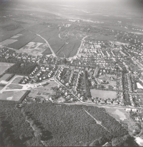 Luchtfoto vanaf het bos Nimmerdor in oostelijke richting. Direkt achter het bos rechts de Stephensonstraat en links de Buurtweg. Op de achtergrond het Bergkwartier.