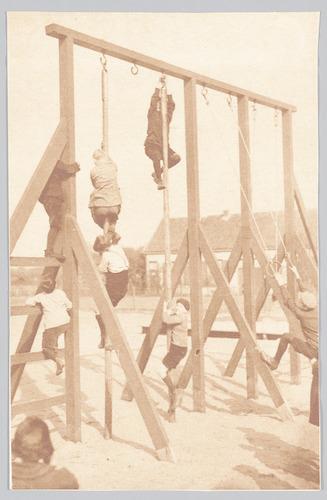"""""""Hiermede publiceeren wij een viertal kieken van de nog niet zoo lang geleden ingewijde kinderspeelplaats in het Leusder kwartier te Amersfoort. De jongens genieten er in de vacanties dubbel. Zie maar eens hoe geanimeerd er in de Paaschvacantie aan het mastklimmen gedaan werd."""""""