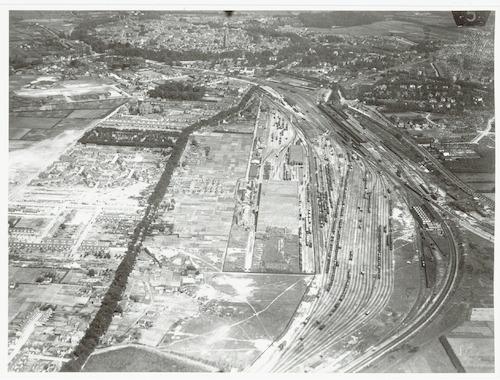 Luchtfoto in oostelijke richting van station en spoorweg emplacement, met delen van het Soesterkwartier (links), de Berg en de wijk Zonnehof (rechts) en het Centrum (boven aan de foto).