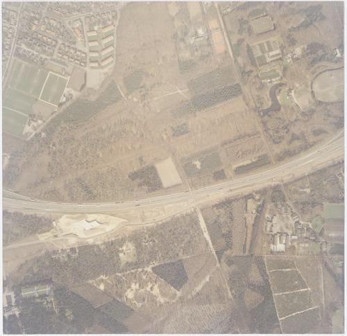Luchtfoto van Nimmerdor en het bosgebied De Treek in Leusden (deels), van elkaar gescheiden door de Rondweg-Zuid. Linksonder zien we het begin van werkzaamheden om deze weg aan te sluiten op de A28. Vlak daarbij (aan de Dodeweg) ligt het Instituut voor Wijsbegeerte en rechtsonder de Technische School Don Bosco. Linksboven nog een deel van het Leusderkwartier.