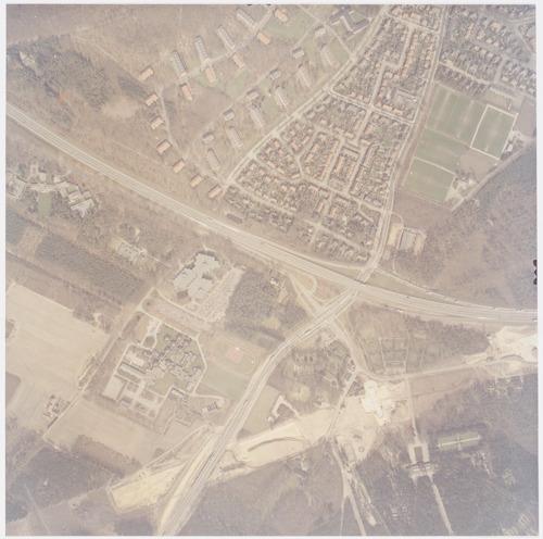 Luchtfoto van de kruising Rondweg-Zuid/Leusderweg. Rechts onderaan zien we de begraafplaatsen Rusthof, Maranatha en Oud-Leusden. Dwars door dit gebied heen loopt het tracé van de toekomstige A28, die in deze tijd werd aangelegd. Links politieschool De Boskamp en het Sinaï-centrum. Bovenaan zien we de wijk Berg (zuid) aan de linkerkant van de Leusderweg en Nimmerdor aan de rechterkant.