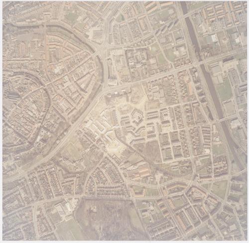 Luchtfoto van de wijk Randenbroek, waar op dat moment het terrein van de Prins Willem III kazerne werd herbebouwd. Ten noorden van de Hogeweg zien we de wijk Kruiskamp; rechts het Valleikanaal; links de Stadskern. Ook de Flierbeek is te ontwaren; deze loopt door het kazerneterrein naar het Valleikanaal. Op de hoek van de Heiligenbergerweg en de Beethovenweg is de Hapam-fabriek te zien. Op het Blekerseiland zijn de oude straten wel gesloopt, maar de wasserijen staan er nog. Bovenaan de foto is ook melkfabriek Amersfortia te zien.