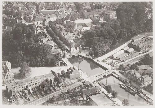 Luchtfoto van de Koppelpoort en omgeving. Op de voorgrond de Eem met spoorbrug, de fabriek van Meursing (rechts) en de Schimmelpenninckstraat (links). Op de achtergrond het Spui.
