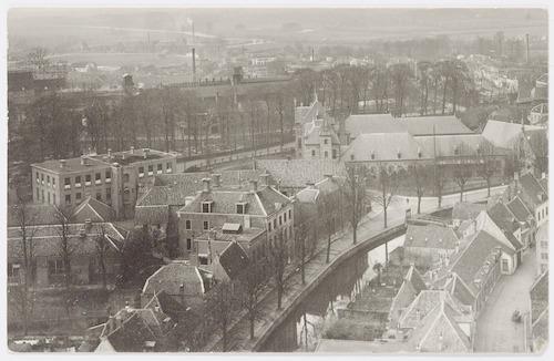 Overzichtsfoto van de Westsingel, vanaf de Onze Lieve Vrouwetoren. Geheel links het gebouw Hellestraat 87 (vanaf 1923 vestiging van de Handelsschool) met daarachter het gebouw van de Ambachtsschool (Achter Davidshof 2). Het hoge gebouw aan de Westsingel is het stadhuis. Daarachter het voormalig Observantenklooster. Meer naar rechts het Sint Pieters en Bloklands Gasthuis. Geheel rechts de Breestraat. Achter de bomen van Plantsoen-West de Meursing-fabriek aan het Smallepad, het Industriekwartier en de Koppel.