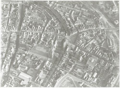 Luchtfoto (1500 f) van de Onze Lieve Vrouwetoren en omgeving. Op het Lieve Vrouwekerkhof ontbreken de bomen; vermoedelijk zijn die in de oorlog gekapt. Links de Langegracht en Kortegracht, in het midden (met een boog) de Westsingel en Zuidsingel, rechts de Varkensmarkt, Arnhemsestraat en Utrechtsestraat. Onderaan de Hellestraat.