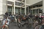 Spui, geparkeerde fietsen bij de ingang van de Openbare Bibliotheek. Rechts Huls…