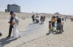 Op het strand van Kijkduin is een bruidspaar op weg naar een strandtent om in he…