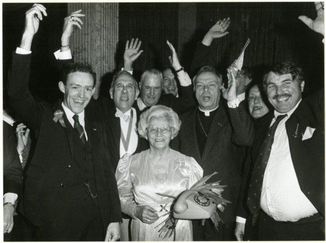 De voorzitter van de vereniging 'Oranje Hofstad', M.H. gravin van Limburg Stirum Hoeufft van Velsen, viert haar 80e verjaardag in hotel Des Indes, Lange Voorhout. Rechts van haar de bisschop van Rotterdam, mgr. drs. R.P. Bär, en geheel rechts jhr. F.F.A. Beelaerts van Blokland; vervaardiger: Konvalinka, Milan; 25 -1 -1986
