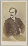 Portret van voren van een man, vermoedelijk genaamd Booth, zittend op een stoel