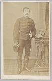Portret van een 2e luitenant der Huzaren rond 1870 staand naast een hekwerk waar…