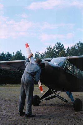 Monteur controleert de motor van een Piper Super Cub.