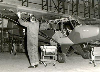 Monteurs aan het werk aan de Piper Super Cub, R-126.