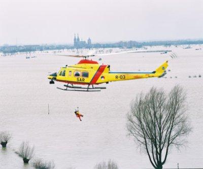 Een Agusta Bell vliegt boven de uiterwaarden.