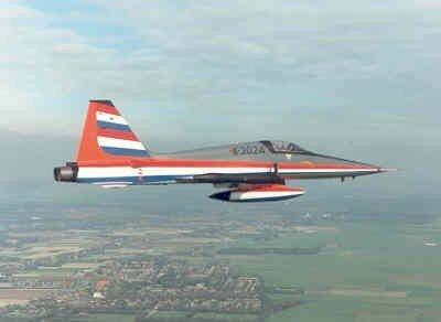 Een van speciale demo beschildering voorziene NF-5A vliegt boven een dorp.