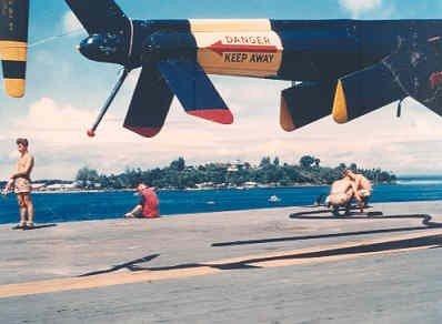 Het vliegkampschip Hr.Ms. Karel Doorman (1948-1968) tijdens de wereldreis van Smaldeel 5 van 31 mei tot 20 december 1960. Het schip op weg naar Sorong. Zicht op het eiland Doom. Aan dek een Air-Sea-Rescue helicopter