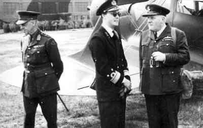 Prins Bernhard arriveert met een Beechcraft 17 Traveller (bijgenaamd Staggerwing) op het vliegveld van Bircham Newton in Engeland, voor een inspectie en het uitreiking van onderscheidingen, 1942. Naast hem (r) de commandant van het vliegveld