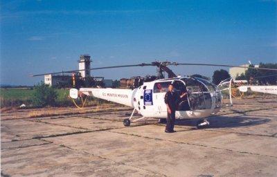 Monteur J. van Bentvelzen wijst op een van de kogelgaten in de Sud Aviation SE.3160/SA.316 Alouette III van ECMM (reg. A-343) op het vliegveld van Zagreb in Joegoslavië. Op de achtergrond het oude stationsgebouw.Op de romp: E.C. Monitor Mission.