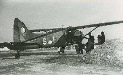 Laden van De Havilland Canada DHC.2 Beaver, registratie S-1, in de sneeuw, voor het bevoorrading van de Waddeneilanden.