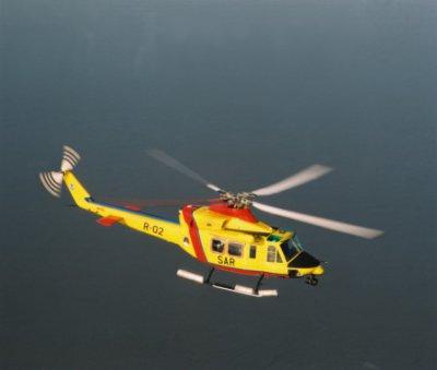 Een Agusta-Bell vliegt boven het water.