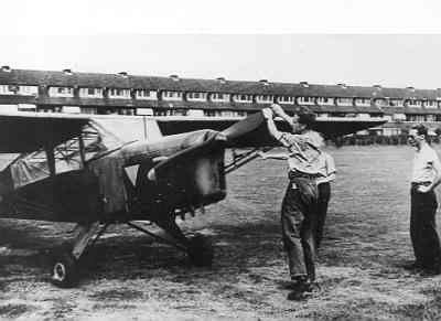 Een Auster  met Engelse kentekens en een oranje driehoek is geland bij Voorburg. Een man staat op het punt de propeller aan te slaan.