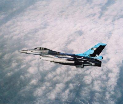 Een F-16 met beschildering '45 years 311 Sqn' vliegt boven de wolken.