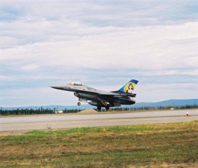 F-16 boven de baan. Op de staart een afbeelding van
