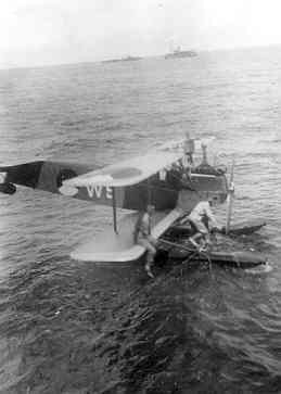 Verkenningsvliegtuig Van Berkel WA (W-5) (1919-1933) met kapotte drijver. Op de achtergrond een jager van de roofdierklasse en Hr.Ms. Serdang