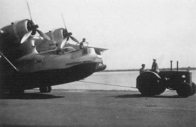 Tractor sleept een Consolidated PBY-5 Catalina maritieme patrouillevliegboot (1941-1957) naar de hangaar te Morokrembangan, Soerabaja