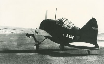 Linksachteraanzicht van een Brewster Buffalo éénmotorig jachtvliegtuig van het Koninklijk Nederlands-Indisch Leger (ML-KNIL) op het gras. Constructienummer NX3180 op het vertikale staartvlak, registratie B-396. Onder de linkervleugel hangt naar alle waarschijnlijkheid een oefenbom van 50 kg.