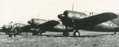 Vijf Brewster Buffalo (ML-KNIL) éénpersoons jachtvliegtuigen op een vliegveld. Hoewel de propellers nog niet draaien, zitten de piloten al wel aan boord. Drie overige militairen staan voor de vliegtuigen. Van de eerste twee vliegtuigen zijn de registraties vermoedelijk B-3102 of B-3103 en B-3106.