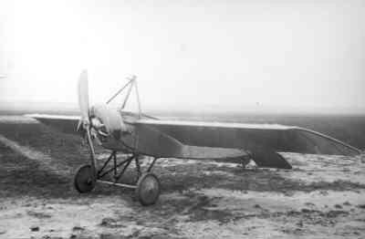 Een Morane L staat op een verder lege vlieghei.