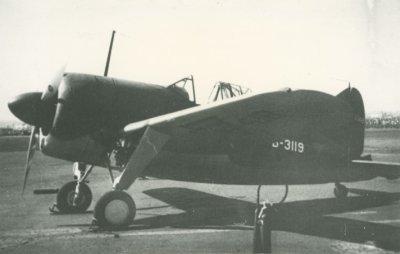 Brewster Buffalo jachtvliegtuig (ML-KNIL), registratie B-3119, op een vliegveld. Voor het vliegtuig staat vermoedelijk een brandblusser.