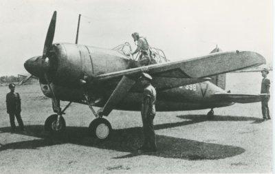 Drie officieren staan op een vliegveld rondom een Brewster Buffalo van het ML-KNIL terwijl de piloot via de linkervleugel in de cockpit van het vliegtuig klimt.