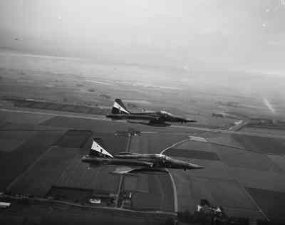 Twee NF-5A's vliegen op lage hoogte boven een agrarisch landschap met een rivier.Op het kievlak van beide toestellen bevindt zich een speciale beschildering bestaande uit drie taps toelopende banen (rood-wit-blauw) met daarin het squadronembleem en de letters NF-5.