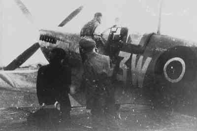 Vlieger zit in de cockpit voor zijn Spitfire. Prinses Juliana kijkt toe en krijgt uitleg. Zij bracht op 26 september 1944 een bezoek aan het squadron.