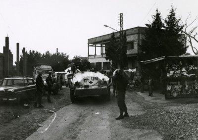 Voertuigen in de dorpsstraat van Haris. Op de achtergrond is de manschappeneetzaal te zien.