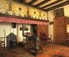 Interieur, overzicht van de brede schouw met gaskachel in de woonkeuken