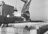 Lossen van een zeeschip met drijvende kraan door Ovet in de...