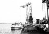 Laden van een binnenvaartschip met drijvende kraan door Ovet in de...