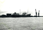 Zeeschip in de Zevenaarhaven. Op de kade liggen kolen en er staan...