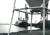 Zeeschip met kraan op de kade en een drijvende kraan van de firma Ovet...