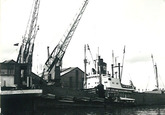 Zeeschip en binnenvaartschip aan een kade in het havengebied van...