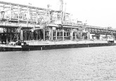 Binnenvaartschepen aan de steiger bij Dow Chemical in de...