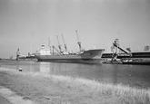 Zeeschip en binnenvaartschip aan de kade bij de Nederlandse Stikstof...