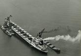 Overslag met drijvende kranen uit een zeeschip in binnenvaartschepen...