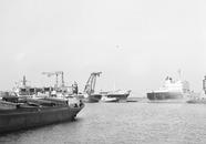 Overslag met drijvende kranen van zeeschip in binnenvaartschip aan de...