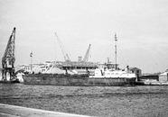 Schip aan de Zuiderkanaalhaven bij bouwmaterialenhandel De Hoop.