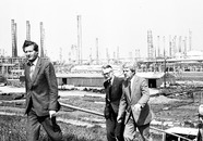 Delegatie van heren staat op de dijk bij Dow Chemical. De derde...