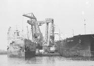 Boord-boord overslag tussen zeeschepen met drijvende kranen bij Ovet...