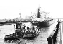 Zeeschip met sleepbote op het kanaal bij brug Sluiskil.